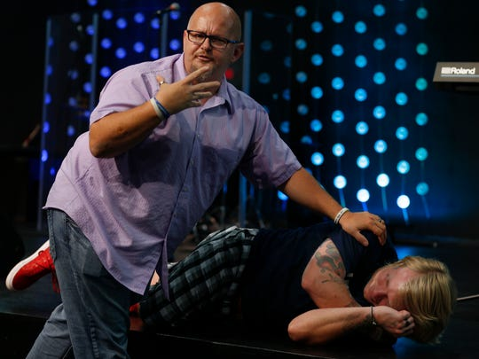 David Stoecker demonstrates how to put a person in the rescue position on an audience member during a training seminar on how to use the lifesaving drug Narcan at CityReach Springfield on Wednesday, Aug, 9, 2017.