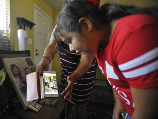 Jazlyn Fisher, 8, watches a video of her father, Eric