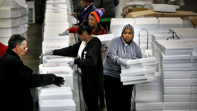 December 8, 2014 - A line of mostly temporary workers packs foodstuffs to be shipped as Corky's begins to ship it's holiday orders Monday morning at Corky's mail order cooking and distribution facility off Brooks Rd. In the next couple of weeks the Memphis based barbecue business will ship over 150,000 packages of frozen food to folks around the country.