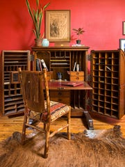 The bold red continues in the adjacent office and highlights the antique Wooton desk with all its cubbyholes and the bearskin rug.