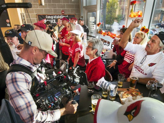"""NFL Cameraman Matt Taylor records Jamie Stock, right, of York, cheering. Stock said he lived a couple blocks from Arians as a child. NFL Films filmed the Bruce Arians' fan club during the Arizona Cardinals game for an upcoming episode of """"A Football Life"""" which focus on the William Penn graduate and current NFL coach and his childhood."""