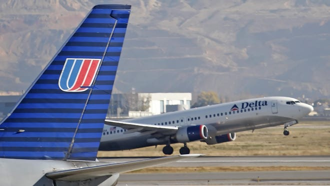 A Delta plane makes its way past a United plane at the Salt Lake City Airport in Salt Lake City, Utah, U.S., on Thursday, Nov. 15, 2007.  Delta Air Lines Inc. said it formed a board committee to review possible mergers as an investor proposed a combination with United Airlines that would create the world's largest carrier.  Photographer: George Frey/Bloomberg News