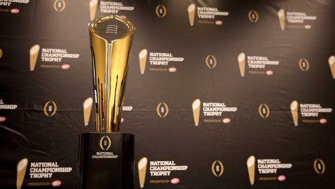 College Football Playoff National Championship Trophy in Irving, Texas. A rising gold football-shaped trophy will be the prize for the national champion in the new College Football Playoff. (AP Photo/Tony Gutierrez)