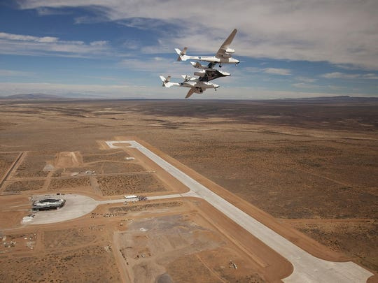 Virgin Galactic's WhiteKnightTwo with SpaceShipTwo attached flying overhead during the dedication of the New Mexico Spaceport Authority Spaceport America on Oct. 22, 2010.