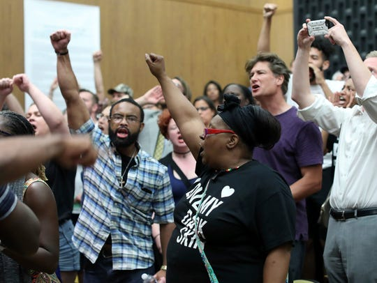 Protesters yell during the Charlottesville City Council