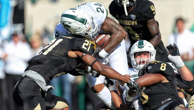 Michigan State Spartans running back Gerald Holmes (24) is tackled by Western Michigan Broncos defensive back Stefan Claiborne (21) and Western Michigan Broncos linebacker Caleb Bailey (8) during the first half of a game at Spartan Stadium.