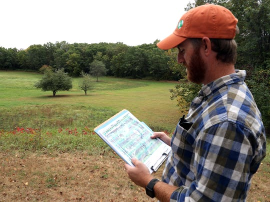 Brian Miner with the Nature Conservancy checks a map showing what is left of the oak savanna in the background at the former Chapman Hills Girl Scout Camp in Walworth County. The Nature Conservancy has acquired the former Girl Scout Camp to preserve the rare oak savanna and other landscape features at the site. The Nature Conservancy last week purchased the 107-acre camp in the headwaters of the Mukwonago River. The Conservancy paid $760,000 for the 107-acre tract. The property will become part of the Conservancy's Crooked Creek Preserve in the Mukwonago River watershed.