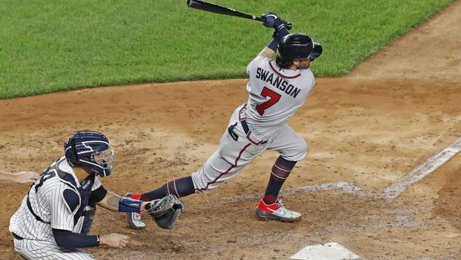 The Atlanta Braves' Dansby Swanson (7) follows through on a seventh-inning single in a Wednesday in New York. New York Yankees catcher Gary Sanchez (24) is behind the plate. The Braves visit the Miami Marlins on Saturday.