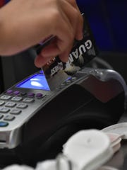 A cashier swipes the Quest card for the Supplemental Nutrition Assistance Program, commonly referred to as the food stamp program.