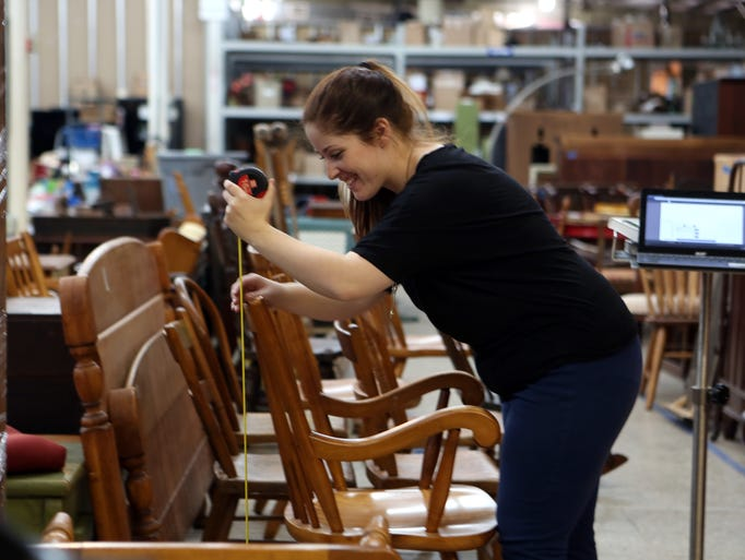 Hilary Lewallen takes measurements of furniture in the cataloging area of Everything But The House.