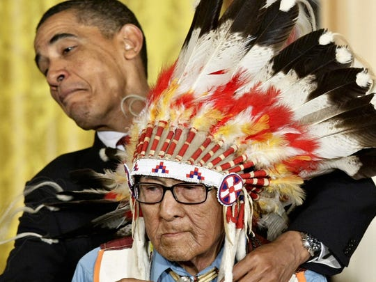President Barack Obama leans away to avoid the headdress as he presents the 2009 Presidential Medal of Freedom to Joseph Medicine Crow during ceremonies at the White House in Washington.