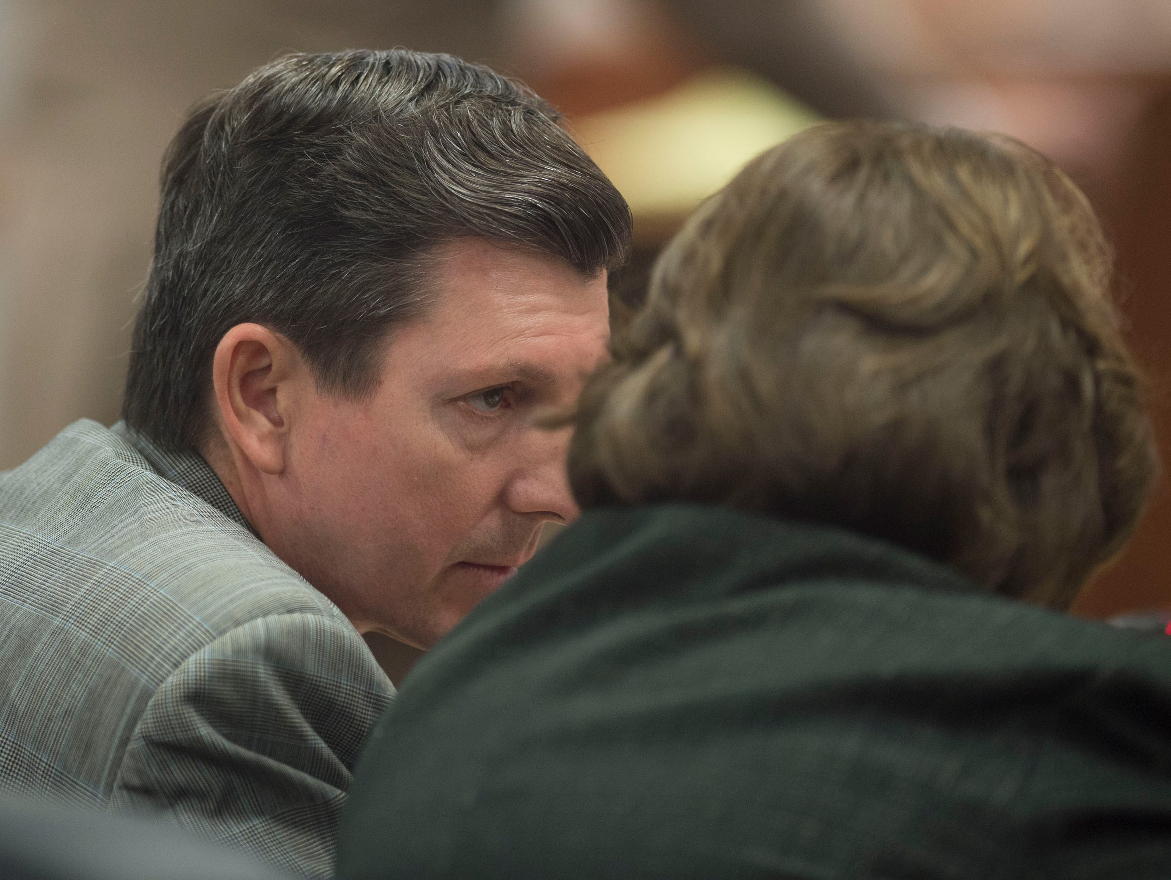 Assistant State Attorney Ryan Butler (left) speaks to retired Assistant State Attorney Lynn Park.