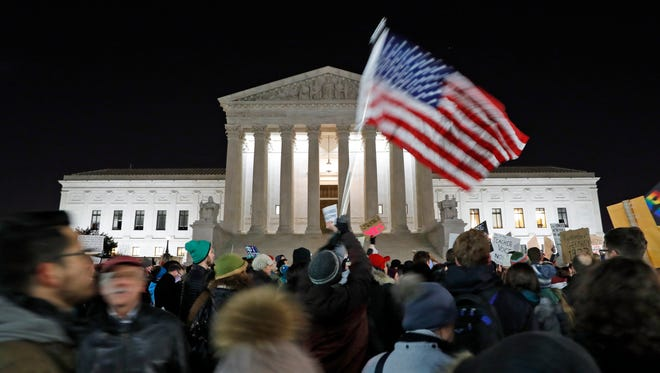 A protester waves an American flag in front of the Supreme Court during a protest about President Trump's recent executive orders in Washington on  Jan. 30, 2017.
