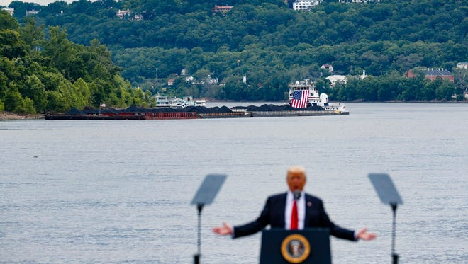In this June 7, 2017 file photo, a coal barge is positioned as a backdrop behind President Donald Trump as he speaks during a rally at the Rivertowne Marina in Cincinnati. President Donald Trump personally promised to activate emergency legal authorities to keep dirty or economically uncompetitive coal plants from shutting down, a top American coal company said. The Trump administration now says it has no plans to do so.  (AP Photo/John Minchillo, File)