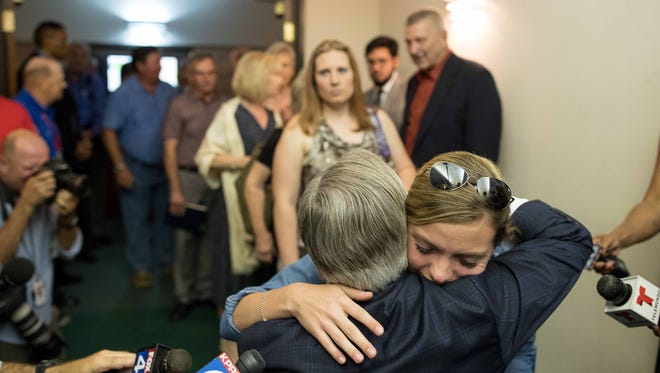 Texas Gov. Greg Abbott hugs a young women in the lobby of the Arcadia First Baptist Church in Santa Fe, Texas before the service on May 20, 2018.