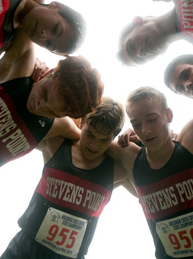 The Stevens Point Area Senior High School cross country team huddles together after placing 8th as a team in the 2015 State Cross Country Championships at the Ridges Country Club in Wisconsin Rapids, Saturday, Oct. 31, 2015.
