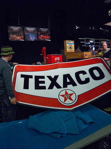Barrett-Jackson employees lift a Texaco Oil service station sign to auction stage at the Barrett-Jackson collector-car auction in Scottsdale on Sunday, Jan. 24, 2016.