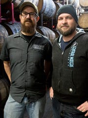 Central Waters owners Paul Graham, left, and Anello Mollica stand among the thousands of oak barrels in the Central Waters warehouse where the brewery's award-winning beers age.