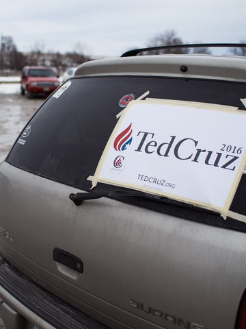 A Ted Cruz sign is affixed to a car window outside