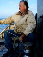 Jerry Serafin works the winch to lift nets full of