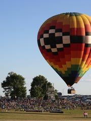 A ride balloon lifts off above the crowd at the National Balloon Classic in Indianola in 2018.