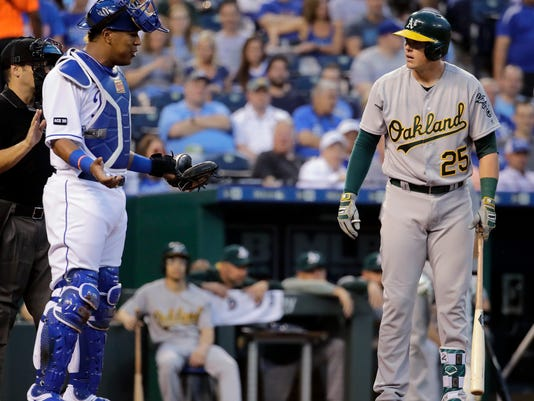 Kansas City Royals catcher Salvador Perez and Oakland Athletics' Ryon Healy (25) talk during Healy's at-bat during the second inning of the teams' baseball game Thursday, April 13, 2017, in Kansas City, Mo. (AP Photo/Charlie Riedel)