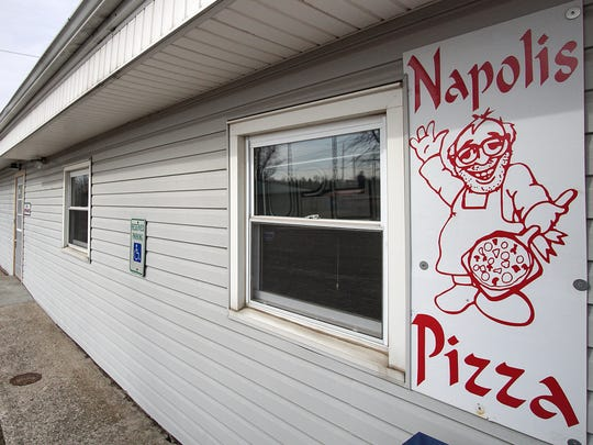 A sign advertising Napoli's Pizza.