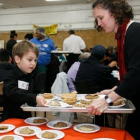 Z Bomsta, 6, of Brighton, helps him mom Heather load up a delivery tray with pie, November 26, 2015, at Cristo Rey Community Center in Lansing.  About 120 volunteers served between 600-800 guests custom ordered dinners.