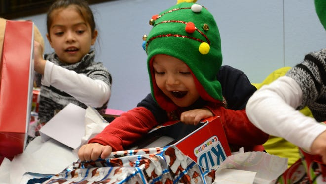 """Flor Rodriguez (left), 8, responds to the excitement of her brother, Evan Rodriguez, 3, opening a Christmas gift from the Oxnard Police Department on Wednesday at the Santa at the Station event. The department """"adopted"""" the two families who were in serious vehicle crashes."""