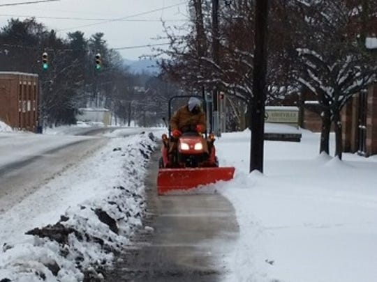 In this file photo, a city of Asheville worker clears snow from walks.