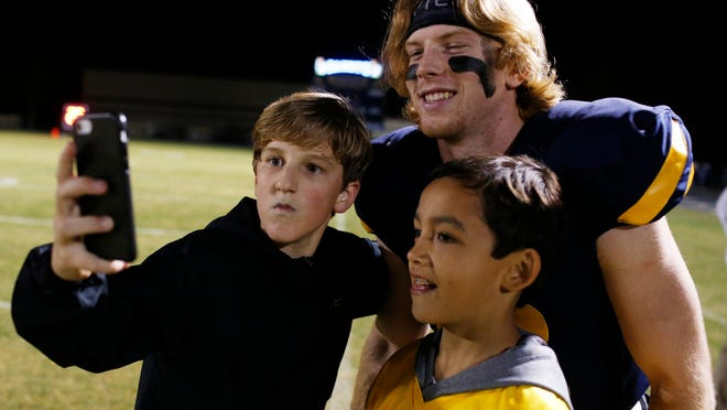 Prince Avenue's Brock Vandagriff (12) takes a photo with the ball boys after winning an GHSA high school football game between Prince Avenue Christian and Athens Christian in Bogart, Ga., on Friday, Nov. 20, 2020. Prince Avenue Christian won 55-9.