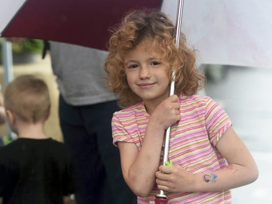 Emily Riddle, 6, of Chambersburg visits the North Square Farmers Market Saturday with her family despite the rain.
