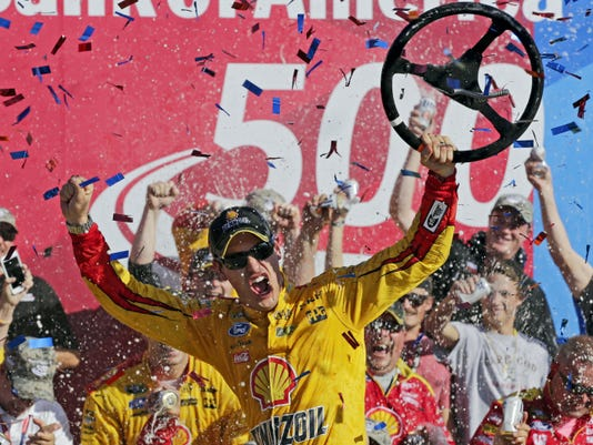 Joey Logano celebrates in victory lane after winning the Bank of America 500 race at Charlotte Motor Speedway in Concord, N.C., on Sunday. The win automatically moved Logano into the third round of the Chase for the Championship playoffs.