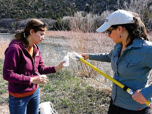 From left, Julia Campus and Melissa May collect a river water sample for a study examining contaminants in the Animas and San Juan rivers in this undated photo.