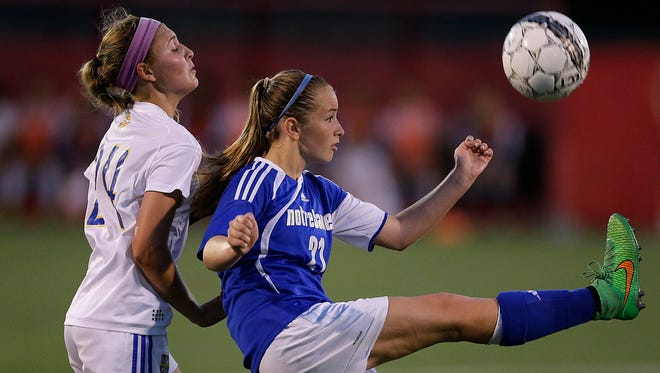 Green Bay Notre Dame midfielder Trudy Quidzinski (21) kicks the ball while being defended by Catholic Memorial midfielder Morgan Rymer (24) in the second half in Thursday night's WIAA Div. 3 semifinal game during the state soccer tournament at Uihlein Soccer Park in Milwaukee.