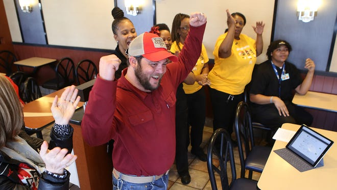 Jonathan Dycus is cheered on after winning the first bottle of Big Mac Special Sauce at McDonald's in Humboldt, Tenn., on Thursday.