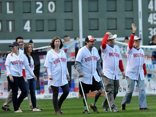 Boston Marathon victim Jeff Baumann and good samaritan Carlos Arredondo walk onto the field as part of pregame ceremonies at Fenway Park.