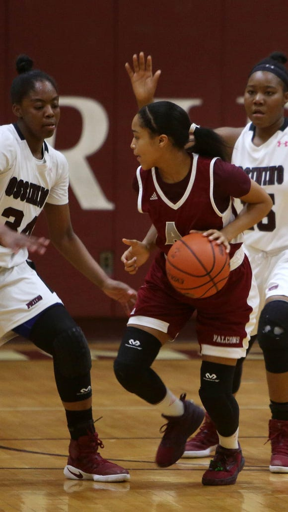 Albertus Magnus' Tanasha Mills tries to dribble around Ossining's Kailah Harris during their game at Ossining High School on Wednesday.