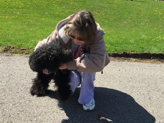 Debbie Caudill greets her dog Sampson after he was