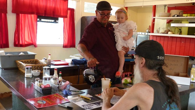 Ken Dalton, owner of The Big Dipper Café, holds his daughter, Delaney Dalton, as he pours a cup of coffee for regular customer Greg Dulik, 61, on Monday. Dalton is closing the restaurant because he can't keep up with the costs while also raising a young child, he said.