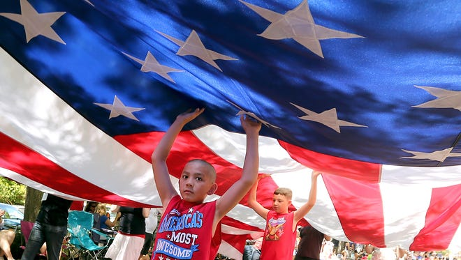 Ira Dagsaan, 9, front, and Greysen Phillips, 11, help carry a giant American flag through downtown Kingston, Wash., as they take part in the annual Fourth of July parade.
