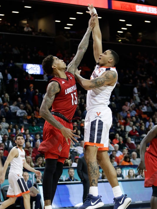 Virginia's Nigel Johnson (23) shoots over Louisville's Ray Spalding (13) during the second half of an NCAA college basketball game in the quarterfinal round of the Atlantic Coast Conference tournament Thursday, March 8, 2018, in New York. Virginia won 75-58. (AP Photo/Frank Franklin II)