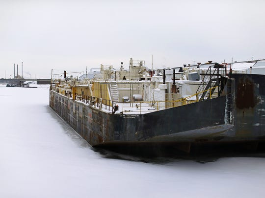 A barge owned by St. Mary Cement sits along the waterfront near the Walnut Street Bridge in downtown Green Bay.