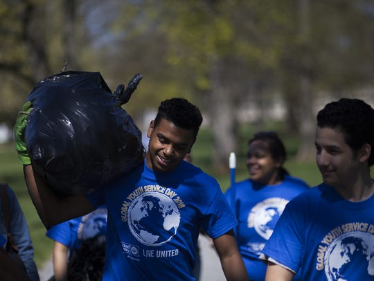 William Penn student Devon Estrada-Wansel, 17, carries a bag of debris, including sticks, leaves and trash, to a central collection area. Students involved in Youth Court Alliance cleaned up Penn Park in York during Global Youth Service Day. Students are documenting their work to help the community as part of a social action project.