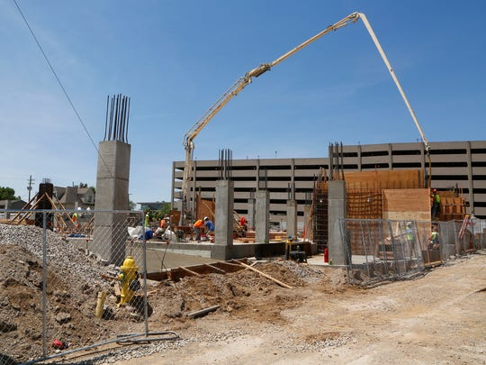 Crews work on the foundation of The Hub, a 10-story