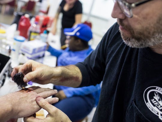 Duane P. Craig applies artificial blood to a hand wound for one of the participants in the Mid-South Emergency Planning Coalition active shooter medical surge exercise Oct. 11, 2017.