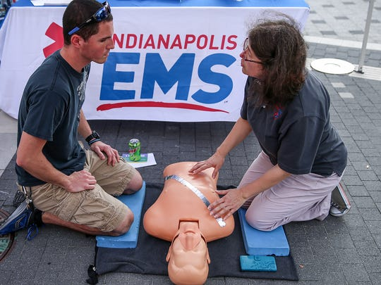 From left, Aaron McConnell learns how to give CPR from Catherine Marriott, with Indianapolis EMS, during the IMPD downtown district community day on Georgia Street, Indianapolis, on Sept. 21, 2017.