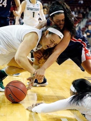 Michigan State center Jasmine Hines, left, and guard Branndais Agee, lower right, reach for a loose ball during the first half in a first-round NCAA Tournament game Friday.