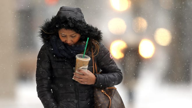 A Morristown woman bundles up against the wind in December.