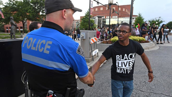 Derrick Quarles stops to shake a Greenville police officer's hand as a group of around 50 protesters marched up Main Street in downtown Greenville during a rally on July 11, 2016.